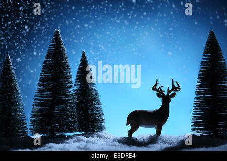 Silhouette of deers and fir tree on Christmas background. - Stock Photo