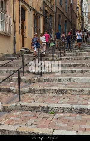 Small group of tourists climbing steps to the Panier district of old Marseille, France. - Stock Photo
