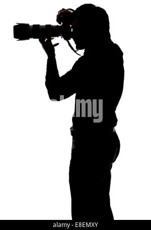 Professional photographer taking a picture in silhouette isolated over white background - Stock Photo