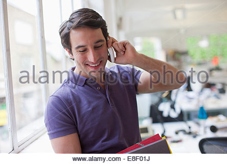 Smiling businessman holding folders and talking on cell phone in office - Stock Photo