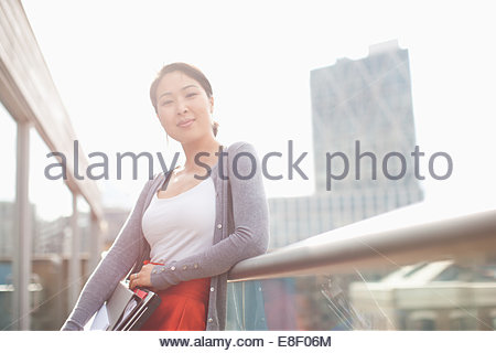 Smiling businesswoman holding folders and leaning on railing of urban balcony - Stock Photo