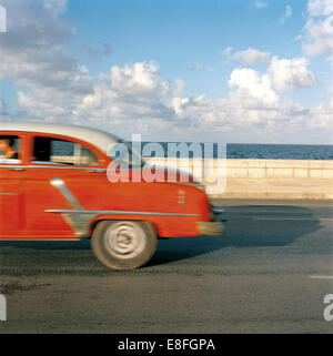 Vintage car driving along Malecon, Havana, Cuba - Stock Photo