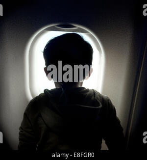 Boy looking through window on airplane - Stock Photo