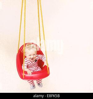 Boy in pyjamas sitting in a swing - Stock Photo