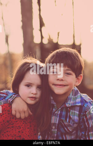 Portrait of sister and brother (2-3, 6-7) in park - Stock Photo