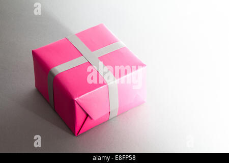 Gift box wrapped in pink paper - Stock Photo