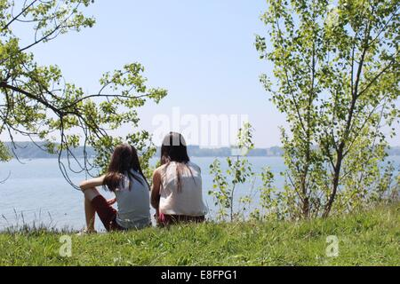 Two girls sitting by river - Stock Photo