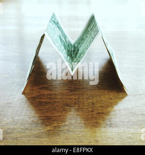 US dollar bill in the shape of the letter M - Stock Photo