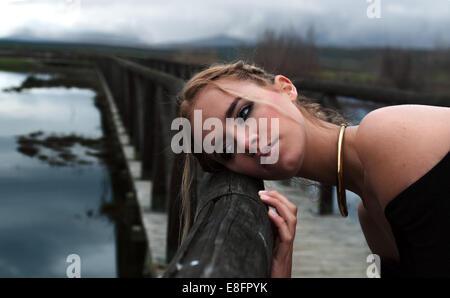Fashion model leaning on railing of bridge - Stock Photo
