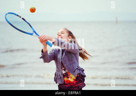 Girl playing tennis on the beach - Stock Photo