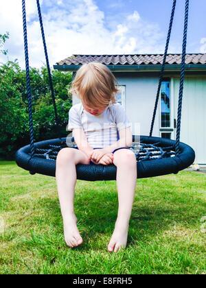 Boy sitting on swing in garden - Stock Photo
