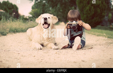 Boy with his dog sitting and photographing with old camera - Stock Photo