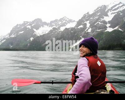 Woman kayaking near glaciers in Kenai Fjords National park, Alaksa, America, USA - Stock Photo