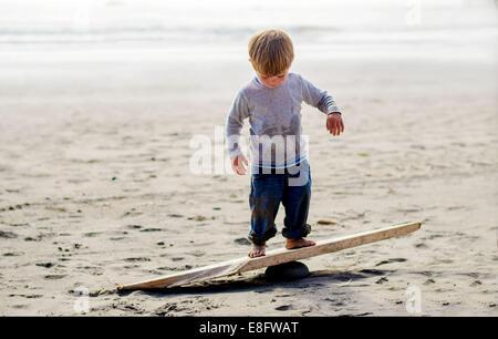 Boy ( 2-3 ) balancing on wooden plank - Stock Photo