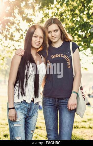 Portrait of confident female high school students standing on schoolyard - Stock Photo
