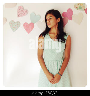 Girl leaning against a wall looking sideways - Stock Photo