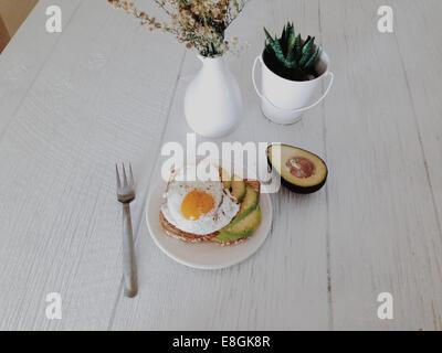 Avocado and fried egg on toast breakfast - Stock Photo