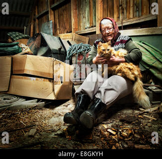 Norway, Old woman in her barn with cat - Stock Photo