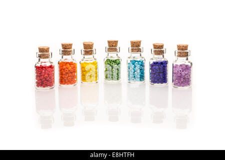 Tiny glass bottles with a cork stopper, filled with a rainbow colours of beads, on a white background - Stock Photo