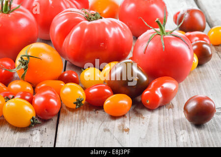 Colorful different kind tomatoes in a bowl on wooden table. Red, yellow, big and small tomatoes. Copy space. - Stock Photo
