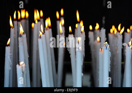 Altar candles in the Cave where Bernadette Soubirous had her Marian apparitions of our Lady of Lourdes in the french - Stock Photo