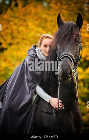 Rider with cape on a Frisian, black horse, gelding - Stock Photo