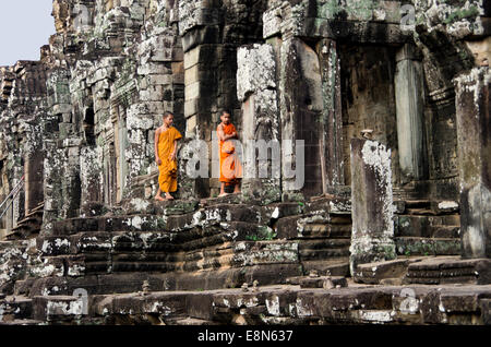 Bayon Temple, Angkor Thom two boy monks climbing on rocks - Stock Photo