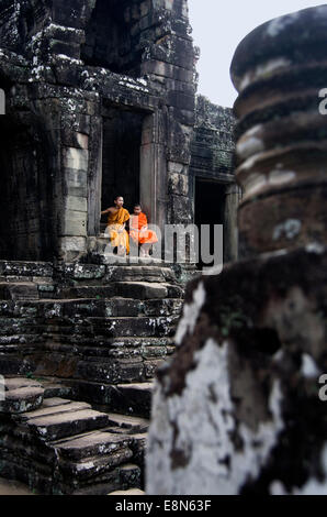 Bayon Temple, Angkor Thom two boy monks sit in doorway - Stock Photo