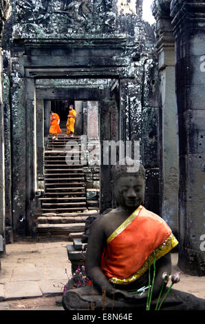 Bayon Temple, Angkor Thom two boy monks climb down stairs, decorated god in foreground - Stock Photo