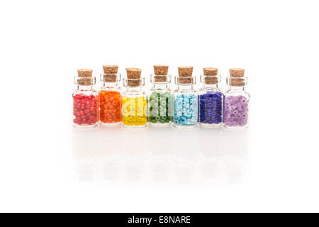 Tiny glass bottles with a cork stopper, filled with a rainbow colors of beads, on a white background - Stock Photo