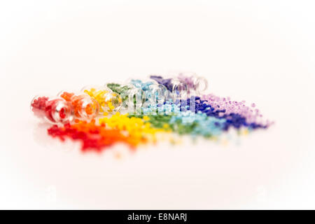 Selective focus tiny glass bottles filled with a rainbow colors of beads spilling out, on a white background - Stock Photo