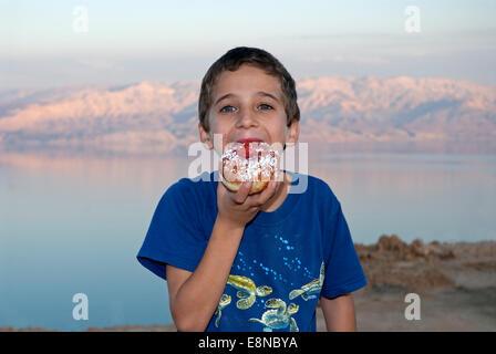 Kid Eating donut near the dead sea , Israel - Stock Photo