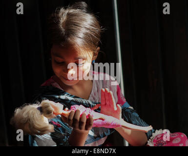"""Pakistani young girl """"Zainab Sajid """" holds Barbie doll as she plays with it on the eve of International Day of the - Stock Photo"""
