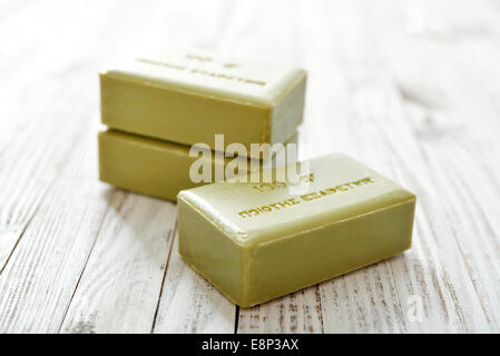 Greek olive soap on wooden background closeup - Stock Photo