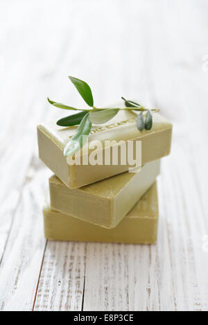 Greek olive soap with olive twig  on wooden background - Stock Photo