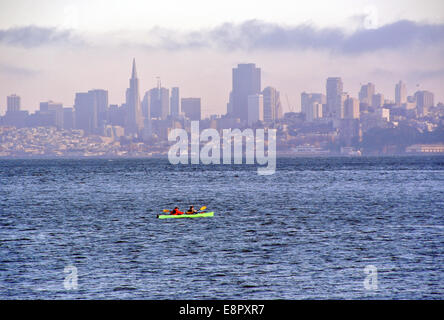 two women paddle kayak on san francisco Bay with skyline in background - Stock Photo