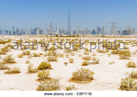 Skyline of skyscrapers and Burj Khalifa from the desert in Dubai United Arab Emirates - Stock Photo