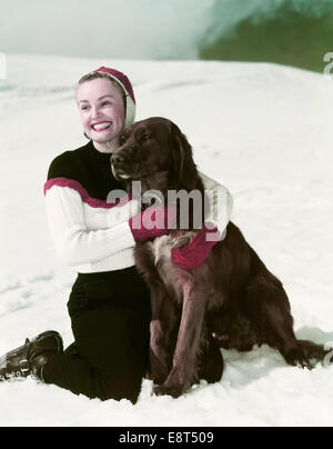 1940s SMILING WOMAN WEARING SKI OUTFIT KNEELING IN SNOW HUGGING IRISH SETTER DOG - Stock Photo
