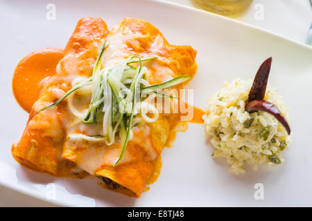 3 enchilada wraps in red pepper sauce, filled with pieces of seafood like oktopus and shrimp. Herbal rice as side - Stock Photo