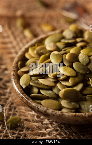 Raw Organic Pumpkin Pepita Seeds in a Bowl - Stock Photo