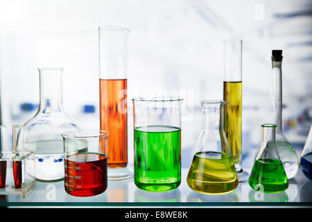 Beakers of various solutions on shelf in lab - Stock Photo