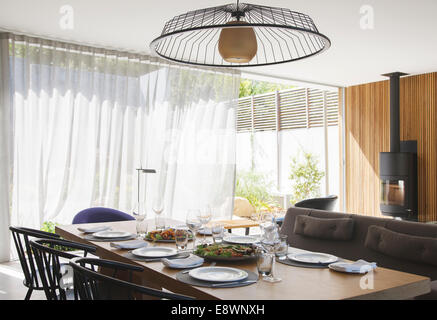 Chandelier over dining table in modern dining room - Stock Photo