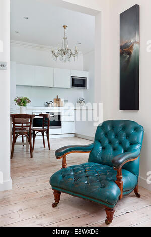 Blue armchair in sitting room with view to modern kitchen, Hove - Stock Photo