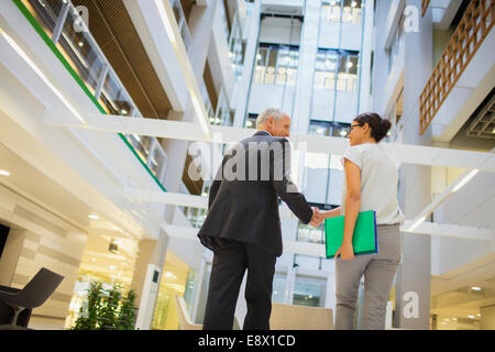 Business people shaking hands in office building - Stock Photo