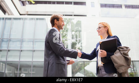 Business people shaking hands outside office building - Stock Photo