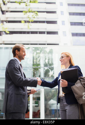 Business people shaking hands outside of office building - Stock Photo