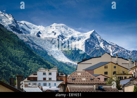 Mont Blanc above the rooftops of Chamonix, French Alps, Savoy, France, Europe with the Glacier des Bossons - Stock Photo
