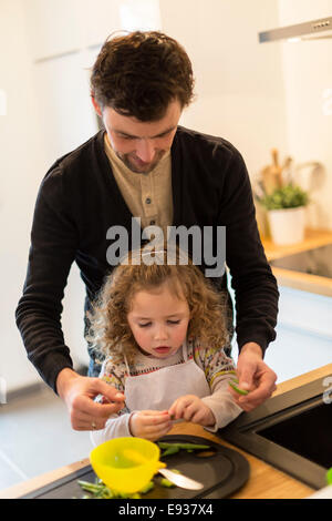 Father and his daughter preparing food - Stock Photo