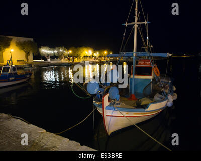 Greek fishing boat and colourful harbour lights, late evening or night in the harbour of  Pythagorion on Samos island - Stock Photo