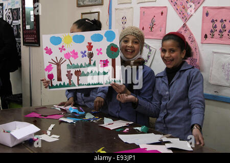 Pupils hold up their art work in a classroom at the Elementary Girls' School No. 2 in the Irbid Palestinian refugee - Stock Photo